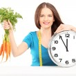 Woman holding carrots and clock — ストック写真