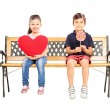 Kids holding heart and lollipop — Stock Photo #45869449