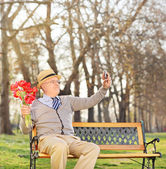 Senior holding flowers and taking selfie — Stock Photo