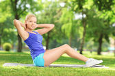 Young female doing exercises on mat in a park — Foto Stock