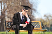 Sad college student in park — Stock Photo