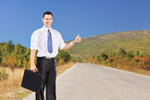 Businessperson hitchhiking on road — Stock Photo