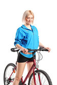 Beautiful smiling female posing next to a bicycle — Stock Photo