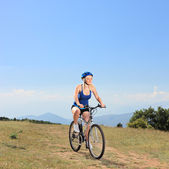 Female biker riding mountain bike — Stock Photo