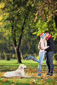 Male and female kissing in park — Stock Photo