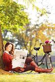 新聞を読んで自転車を持つ女性 — ストック写真