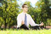 Businessperson meditating on a grass — Stock Photo