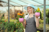 Female gardener holding flower pots — Stock Photo