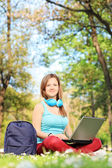 Woman in park and working on laptop — Stock Photo