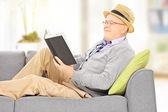Senior man reading a novel — Stock Photo