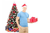 Guy with santa hat holding gift — Stock Photo