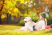 Female lying on grass with dog — Stock Photo