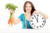 Woman holding carrots and clock — Stock Photo