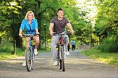 Happy couple biking in park — Stock Photo