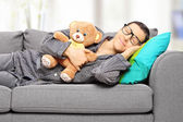 Man holding teddy bear and taking a nap — Stock Photo