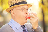 Senior man taking asthma treatment — Stock Photo