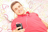Man on bed listening music from phone — ストック写真