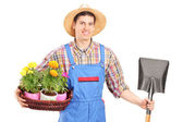 Agricultural worker holding shovel and flowers — Stock Photo