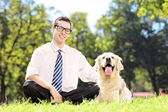 Guy sitting next to dog in park — Photo