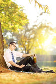 Disappointed man with bottle in park — Stock Photo