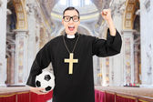 Priest holding football and cheering — Stock Photo