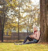 Dívka sedící strom v parku — Stock fotografie