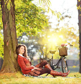 Female with bicycle relaxing in a park — Stock Photo