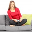 Female on a couch and playing video game — Stock Photo #45871181