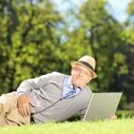 Senior man on grass working on laptop — Stock Photo #45871611