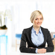 Blond smiling businesswoman sitting at her desk — Stock Photo #45872349