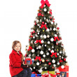 Girl sitting next to christmas tree — Stock Photo #45875083