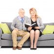 Couple seated on sofa reading book — Stock Photo #45875761