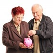 Couple putting coin into piggy bank — Stock Photo