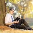 Man reading a book in park — Stock Photo