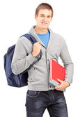 Male student holding backpack and books — Zdjęcie stockowe