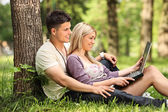 A boyfriend and girlfriend working on a laptop — Stockfoto
