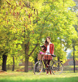 Female with bicycle in a park — Stock Photo