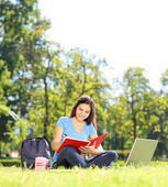 Student writing in notebook outdoors — Stock Photo