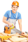 Worker cutting wooden batten with saw — Stock Photo