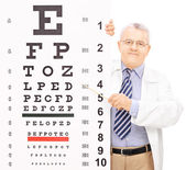 Optician pointing to an eyesight test — Stock Photo
