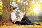 Male reading a newspaper in a park — Foto de Stock