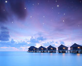 Starry skies over water villa cottages — Stock Photo