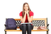 Unhappy female student sitting on a wooden bench — Stock Photo