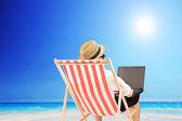 Man working on a laptop on beach — Stock Photo