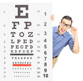 Man with glasses peeking behind eyesight test — Stock Photo