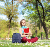 Beautiful young female student with book and headphones — Stock Photo
