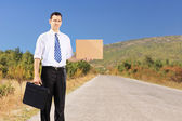 Businessman hitchhiking — Stock Photo