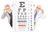 Woman and optician standing behind eyesight test — Stock Photo
