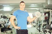Muscular man lifting weight — Stock Photo