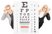 Woman and mature behind eyesight test — Stock Photo